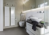 A wash stand with a bowl basin, a corner toilet and a designer radiator in a small bathroom