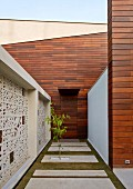 Courtyard of contemporary, Indian house with wood-clad façade and traditional Jali (perforated stone screen)