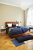 Elegant wooden bed with blue bed linen in bedroom with herringbone parquet floor