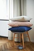 Stacked cushions on retro stool on oak parquet floor