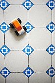 Wooden toy car on traditional white floor tiles with blue ornamental accent tiles
