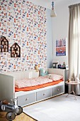 Grey and white wooden bed with storage drawers and orange fitted sheet against patterned wallpaper in child's bedroom