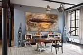 Tabletop on extravagant metal base and modern artwork on grey wall in loft apartment