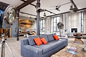 Grey sofa with orange scatter cushions flanked by studio standard lamps in loft apartment with black metal pillars