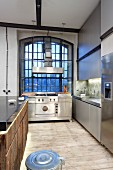 Küche in Edelstahlausführung vor Fabrikfenster in einer Loft-Wohnung