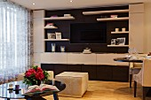 Einbauwand mit Flatscreen in klassisch elegantem Wohnraum mit samtgepolsterten Sitzhockern