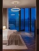 Schlafzimmer mit Blick durch Fensterfront auf Londoner in Abenddämmerung; Retroleuchte mit Leuchtstoffring