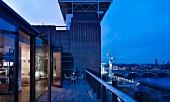 Twilight on roof terrace of penthouse apartment with view of the river Thames