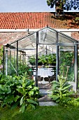 Seating area with white tablecloth on Tulip Table and garden plants in greenhouse with large foliage plants around door
