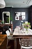 weiße Stühle mit Lochmuster um rustikalen Holztisch im Esszimmer mit schwarz getönten Wänden und weisser Stuckdecke