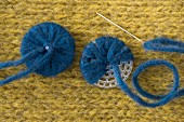 Buttons being made with the blue alpaca mixed yarn