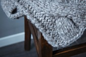A cable knitted blanket made from a woollen mixed yarn (close-up)