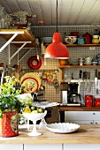 Corner of vintage-style kitchen with red pendant lamp above counter and utensils hung on wall