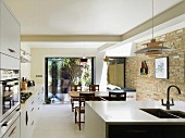 Open-plan, modern kitchen with traditional dining area, old brick wall and view of summer terrace seating area
