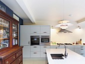 Antique, glass-fronted cabinet in open-plan, white kitchen with designer pendant lamp