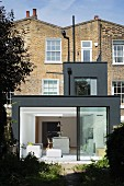 Modern, dark grey extension to Georgian terrace house with open sliding glass wall leading to garden