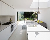 White, designer kitchen with counters, sunlight falling through skylight and view into summery garden