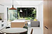 Open-plan, designer-style interior with open sliding French doors and view into green, summery garden