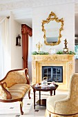 Comfortable, elegant seating area with antique seating and coffee table in front of fireplace below gilt-framed mirror