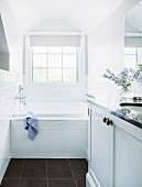 Narrow, white bathroom with vanity units and built-in bathtub in front of the window