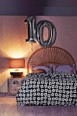 Double bed with a curved headboard made of bamboo, with decorative numbers made of silver balloons