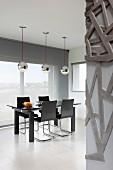 Black dining set on white, tiled floor below shiny, silver pendant lamps in designer interior