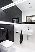 Designer bathroom with white floor tiles, black wall tiles and mirrored wall above sink