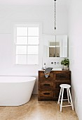 Vintage vanity furniture made of rustic wood in the corner of a bathroom next to a free-standing white bathtub
