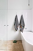 Freestanding bathtub in floor-level shower area with black and white striped towels on white tiled wall