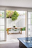 View through open patio door to outdoor dining area in front of white picket fence