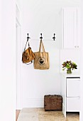 Nostalgic wall hook strip with hanging pockets next to a white cupboard