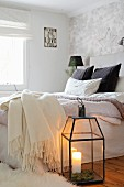 Candle lantern and fleecy blankets in cosy bedroom