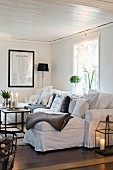White sofa with many scatter cushions in cosy living room