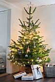 Beleuchteter Weihnachtsbaum mit schlicht verpackten Geschenken