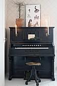 Altes schwarzes Klavier mit Kerzenbeleuchtung
