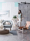 Round upholstered table on woven carpet, sofa and Scandinavian armchair with leather seat, woman against wall with wallpaper strips