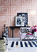 Coffee table in polyhedron form and maritime woven carpet in front of a sofa, black and white decorative objects, wall graphics with pastel colored squares