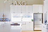 White fitted kitchen with decorative letters on wall cupboards