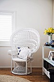 Asian rattan peacock chair painted white in the corner of the room
