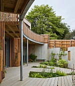Modern, shared, eco-home with encircling balcony and wooden deck with recessed beds of plants