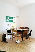 Simple dining area with various chairs and emergency exit sign on wall in corner of minimalist room with old, well-tended wooden floor