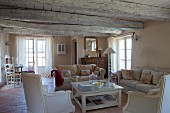 Pale antique armchairs and sofa set in open-plan living area of Provençal country house with whitewashed wood-beamed ceiling