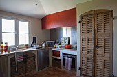 Rustic masonry kitchen counter below window and fitted cupboard with wooden louvre doors