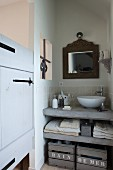 White modern basin on concrete washstand counter with concrete shelf and vintage wooden crates below