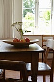 Fruit bowl and vase of flowers on wooden table in front of window