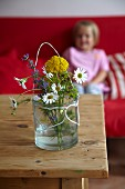Wild flowers in glass of water on wooden table; little girl sitting on sofa in background