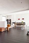 Weisser Wohnraum mit dunklem Dielenboden, im Hintergrund Klassiker Bürostühle an Tisch