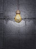 Glühbirne mit Goldverzierung vor grauer Betonwand hängend