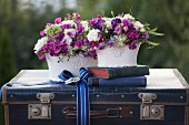 Two romantic flower arrangements and antiquarian books on vintage suitcase decorated with ribbon