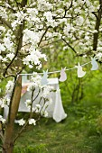 Garland of bunnies between blossoming fruit trees and set table in background